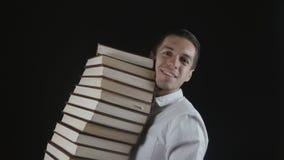 O homem em uma camisa branca está guardando uma pilha de livros em suas mãos em uma sala escura Homem de negócios novo com os liv filme
