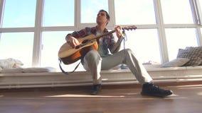 O homem em uma camisa joga uma guitarra acústica em uma sala ensolarada video estoque