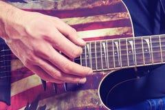 O homem em uma camisa preta e em calças de brim joga uma guitarra acústica fotos de stock royalty free