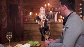O homem em uma data escuta para viver o desempenho do saxofone e olha sua mulher video estoque