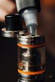 O homem em uma loja do vape está enchendo um líquido especial no e-cigarro Fotografia de Stock Royalty Free