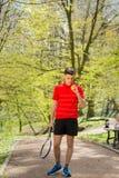 O homem em uma pose vermelha do t-shirt com uma raquete de t?nis e uma bola no fundo do parque verde Conceito do esporte imagens de stock