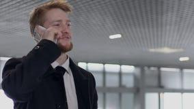 O homem empreendedor novo está falando no telefone, estando no auto salão de beleza vídeos de arquivo