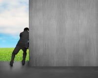 O homem empurra afastado o muro de cimento Fotos de Stock