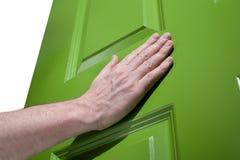 O homem empurra uma porta verde aberta Fotos de Stock Royalty Free