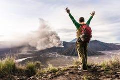 O homem encorajador no monte está olhando na erupção do vulcão de Bromo Imagem de Stock Royalty Free