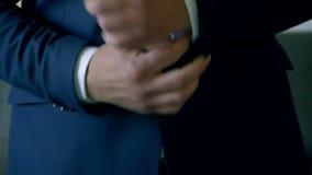 O homem endireita os punhos de sua camisa vídeos de arquivo