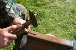 O homem endireita pregos oxidados com um martelo Fotografia de Stock Royalty Free