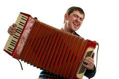 O homem engraçado canta e joga no acordeão Imagens de Stock
