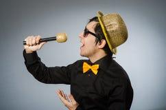 O homem engraçado com o mic no conceito do karaoke Fotos de Stock