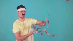 O homem engraçado com um bigode joga o dinheiro e olha a câmera filme