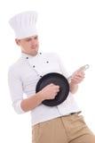 O homem engraçado na frigideira de jogo uniforme do cozinheiro chefe gosta de um isola da guitarra Imagem de Stock