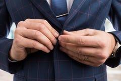 O homem entrega o botão do revestimento do terno de negócio da asseguração foto de stock royalty free