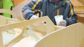 O homem entrega o close up Segura as emendas do barco com colagem de cola Epoxy para a tensão O barco é feito à mão vídeos de arquivo