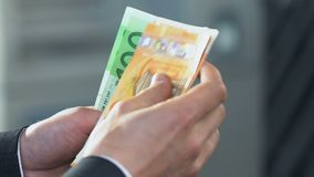 O homem entrega a descrevendo seu salário, guardando o euro- contas, corte no orçamento e economia video estoque