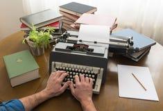 O homem entrega a escrita em uma máquina de escrever velha fotografia de stock