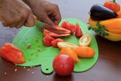 O homem entrega o corte de tomates e de pappers maduros em fatias no cutt Fotografia de Stock