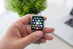 O homem entrega o relógio esperto do toque com apps dos ícones da tela home Imagem de Stock Royalty Free