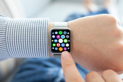 O homem entrega o relógio esperto do toque com apps dos ícones da tela home Foto de Stock Royalty Free