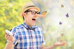 O homem entusiasmado libera borboletas do frasco fora Fotografia de Stock