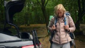 O homem envelhecido de inquietação que ajuda sua esposa a vestir o turista backpack video estoque