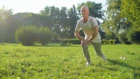 O homem envelhecido desportivo que faz os pulmões exercita no parque vídeos de arquivo