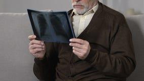 O homem envelhecido na reabilitação que olha os pulmões raio X, virou sobre a doença incurável, saúde vídeos de arquivo