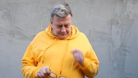 O homem envelhecido na roupa brilhante do que virada, decola seus vidros vídeos de arquivo