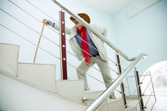 O homem escala as escadas com a dor no seu para trás Imagens de Stock Royalty Free