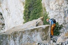 O homem escala uma rocha imagem de stock