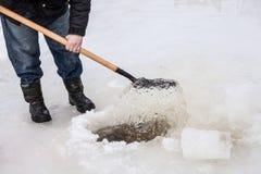 O homem escava o gelo dos pedaços fora do furo Imagens de Stock Royalty Free