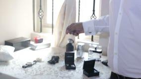 o homem escolhe acessórios vestir para a cerimônia de casamento vídeos de arquivo