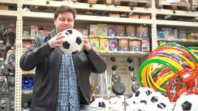 O homem escolhe bens ostentando na loja vídeos de arquivo