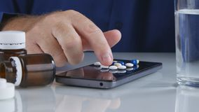 O homem escolhe e toma comprimidos médicos para a dor de cabeça da superfície da tela do telefone celular foto de stock