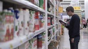 O homem escolhe o suco no supermercado filme