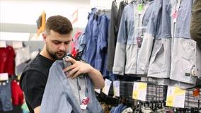 O homem escolhe a roupa dos esportes em um estudante que novo do shopping da loja a compra da roupa ocasional checkout pagar video estoque