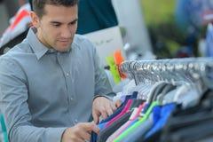 O homem escolhe o t-shirt na loja fotos de stock