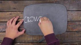 O homem escreve a palavra CROWDFUNDING com giz em um quadro, estilizado como um pensamento vídeos de arquivo