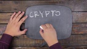 O homem escreve a palavra CRYPTOCURRENCY com giz em um quadro, estilizado como um pensamento video estoque