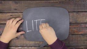 O homem escreve a palavra LITECOIN com giz em um quadro, estilizado como um pensamento filme