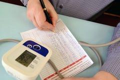 O homem escreve para baixo indicadores no diário do controle da pressão arterial Fotos de Stock Royalty Free
