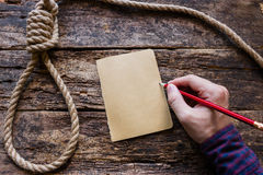 O homem escreve uma nota de suicídio fotografia de stock royalty free