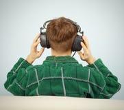 O homem escuta a música sinfónica em casa no sofá fotos de stock royalty free