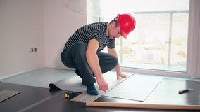 O homem especializado com capacete vermelho coloca a esteira do secundário-revestimento no apartamento novo vídeos de arquivo