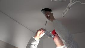 O homem especializado do eletricista instala a luz conduzida moderna no furo do teto video estoque