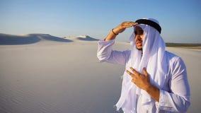 O homem esplêndido do xeique dos UAE do Arabian olha duramente na distância e medita, estando no meio do deserto largo no dia de  video estoque