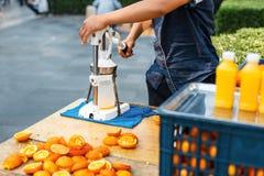 O homem espreme o suco de laranja outdoors imagens de stock royalty free