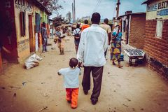 O homem está andando com sua criança na rua em África fotografia de stock royalty free