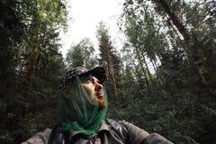 O homem está andando na floresta que densa o viajante farpado com trouxa obteve perdido fotografia de stock royalty free