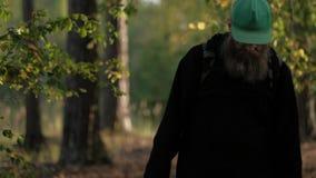 O homem está andando no parque Olha diretamente nos olhos vídeos de arquivo
